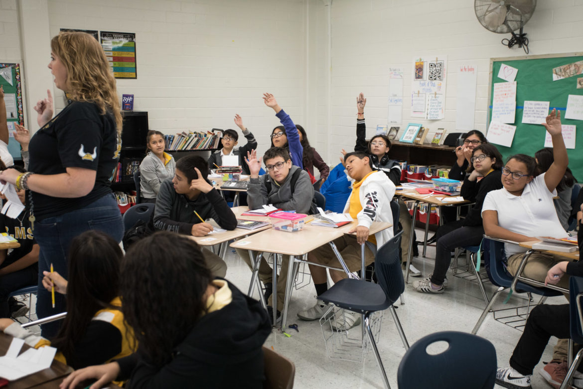 Brentwood Middle School students raise their hands in teacher Megan Prado's seventh grade integrated reading and writing course.