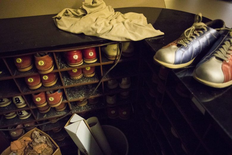 Vintage bowling shoes line the desk of the bowling alley.