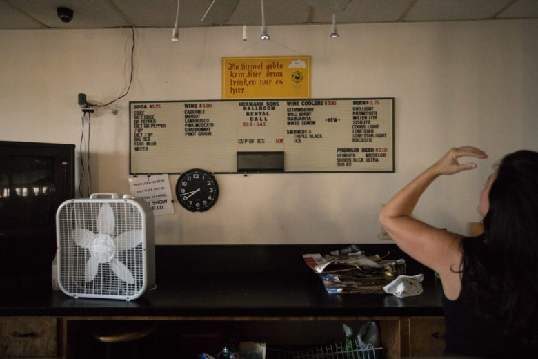 Lori McCorquodale Todd, Hermann Sons Life Home Association board member, gestures to old signage in the ballroom.