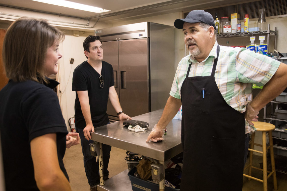 (From left) Lori Chidgey, Corazon Ministries executive director; Gavin Rogers, Associate Pastor of Travis Park United Methodist Church; and John Chadwell, Corazon Ministries kitchen manager, chat in the kitchen before serving food.