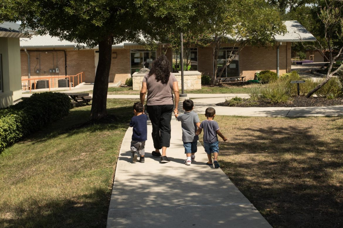 Three boys walk through the Children's Shelter property.