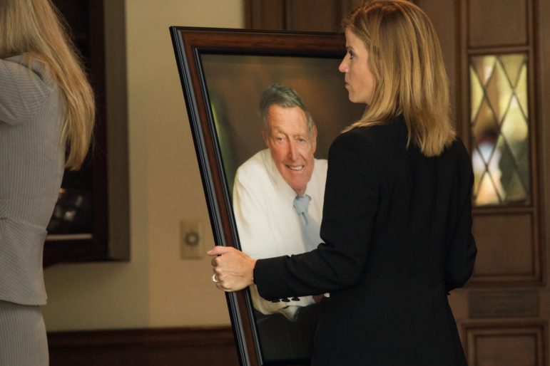 Porter Loring Mortuaries President Helen Loring Dear carries a photograph of Tom Frost.