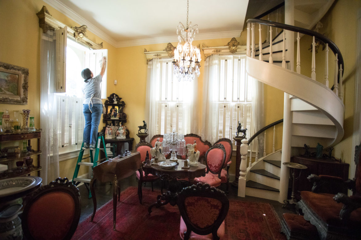 Sylvia Gonzalez-Pizana, Villa Finale manager of collections and interpretation, cleans the Yellow Room in Villa Finale: Museum & Gardens.
