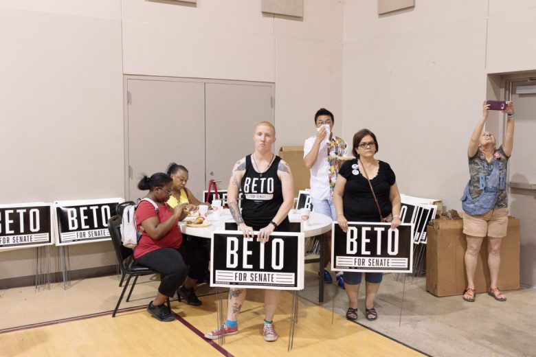 Volunteers and attendees at the Beto O'Rourke town hall watch the congressman's speech.
