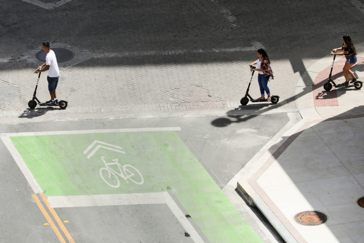 Riders use electric scooters on sidewalks near Main Plaza.