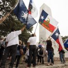 Flags are waved in protest of the long term lease with the City of San Antonio for the Alamo Property next to the cenotaph.