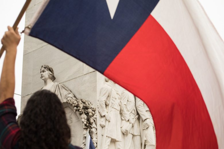 A woman waves a Texas flag next to the cenotaph.