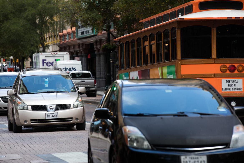 Vehicles travel along Houston Street near the Majestic Theatre.