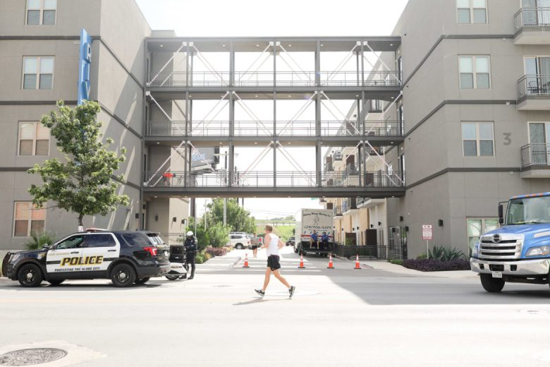 Joggers pass by large apartment complexes that have been built on Broadway in recent years.