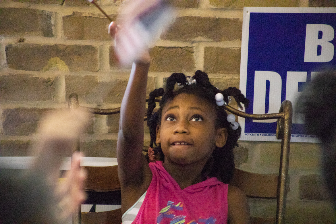 Hileigh Mcdavid, 10, waves a small American flag in the air for Beto O'Rourke.