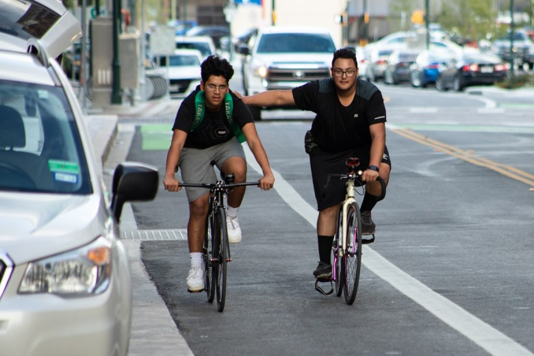 Two cyclists ride down Main Avenue.