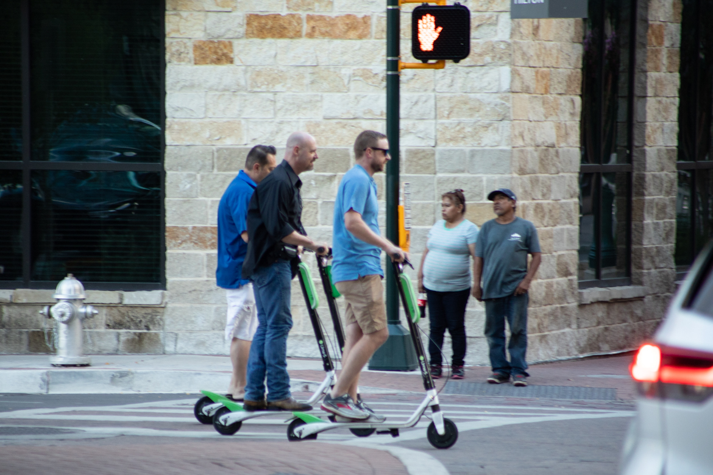 People on scooters ride down Soledad Street.