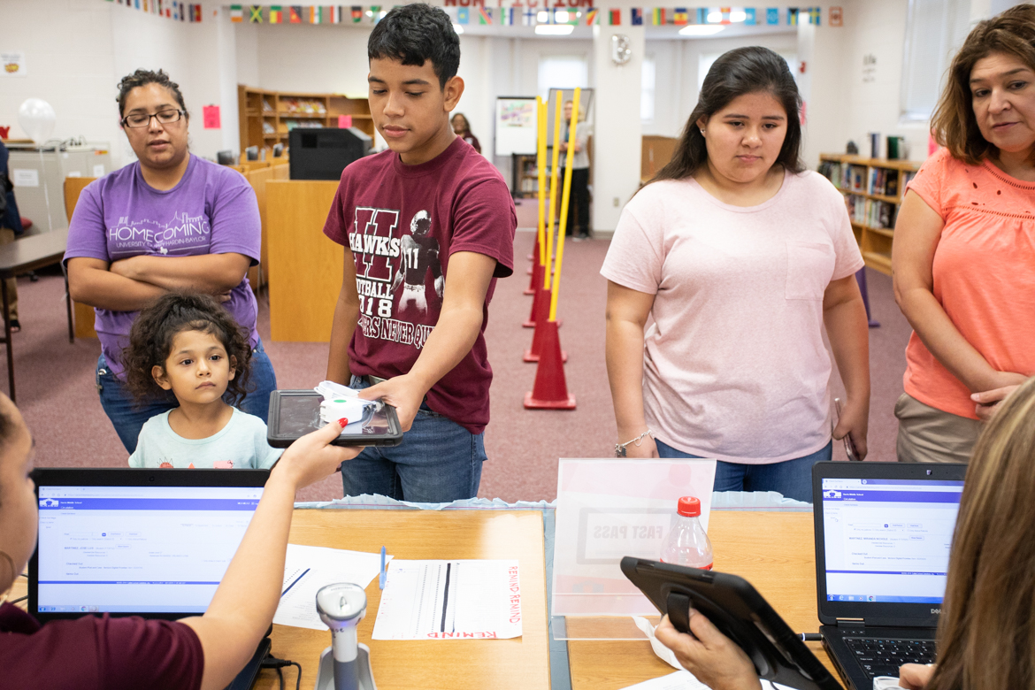 (From left) Harris Academy students Jose Martinez and Miranda Martinez receive their iPads at the device check out.