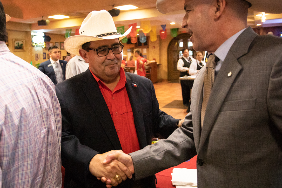 Republican Peter Flores, running for the Senate District 19 seat, (left) shakes hands with his campaign supporters before early voting is completed at his watch party on September 18, 2018.