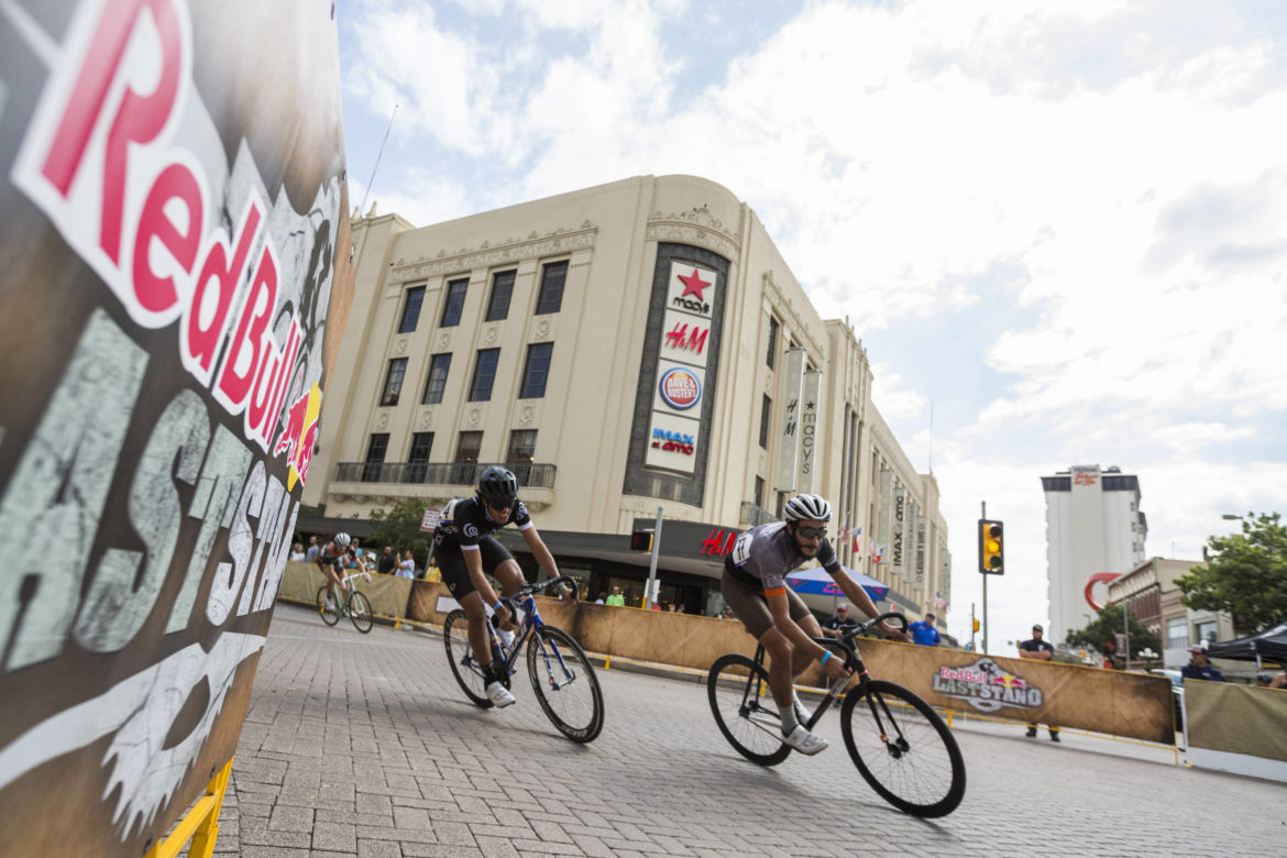 Fixed gear cyclists race by the Joske's building in Alamo Plaza during the Red Bull Last Stand in 2017.