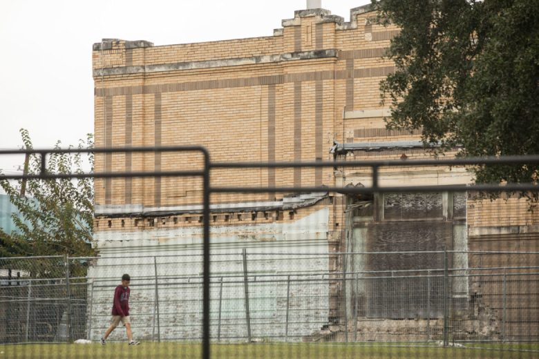 A student runs past the 1915 Beacon Hill Elementary School building, which sits vacant on the grounds of Beacon Hill Academy.