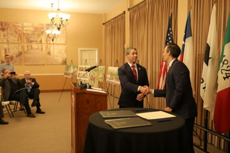 Mayor Ron Nirenberg (left) and Texas Land Commissioner George P. Bush sign a resolution to approve the Alamo Master Plan.
