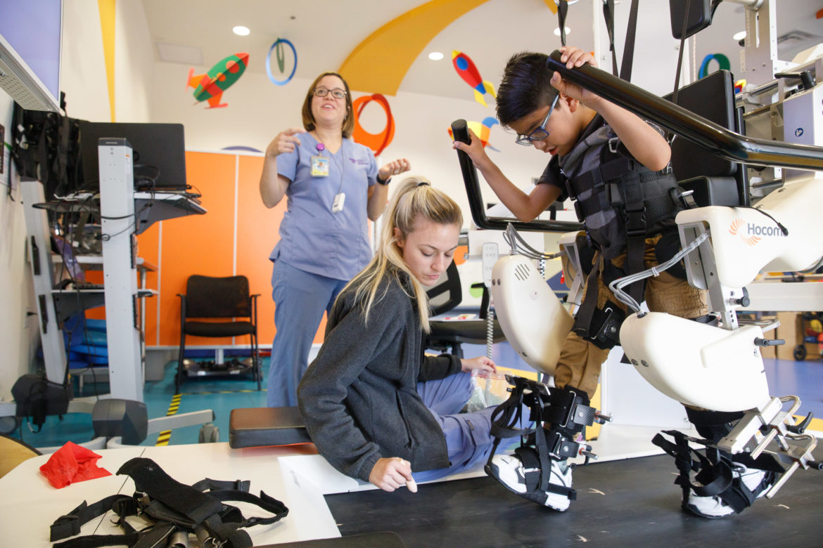 Emanuel Arguelles Silva, 7, walks on a lokomat as specialists aid him in the therapy.