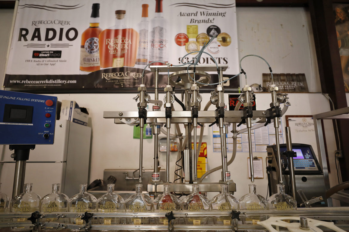 Bottles of Rebecca Creek Whiskey are filled on the assembly line.