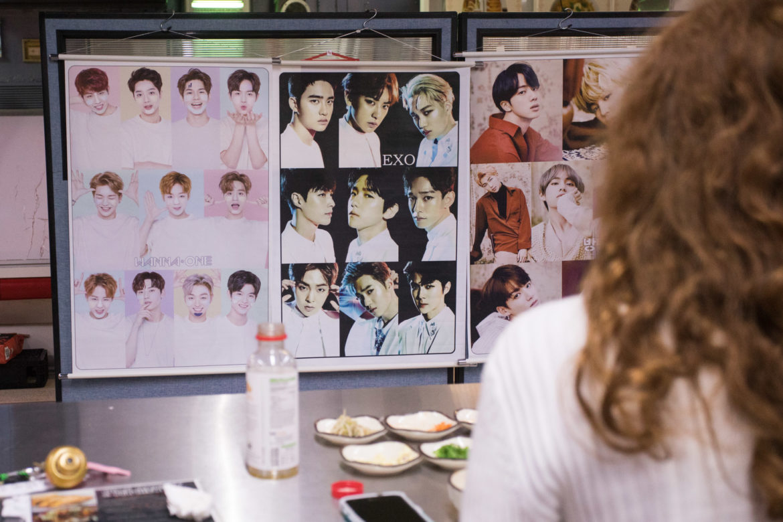 Kristen Elise enjoys a meal in front of of some Korean images.