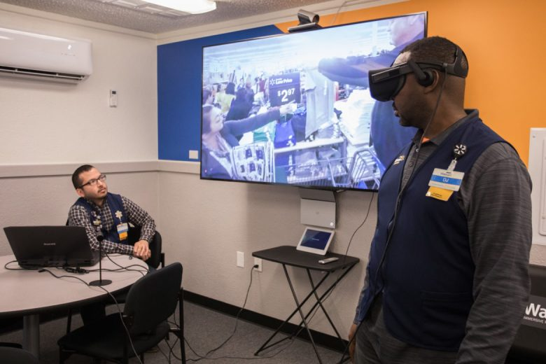 Walmart Academy Facilitator DJ Ddungu (right) uses a VR headset to watch Walmart during the holidays as Walmart Academy Facilitator Robert Segovia instructs his movements.