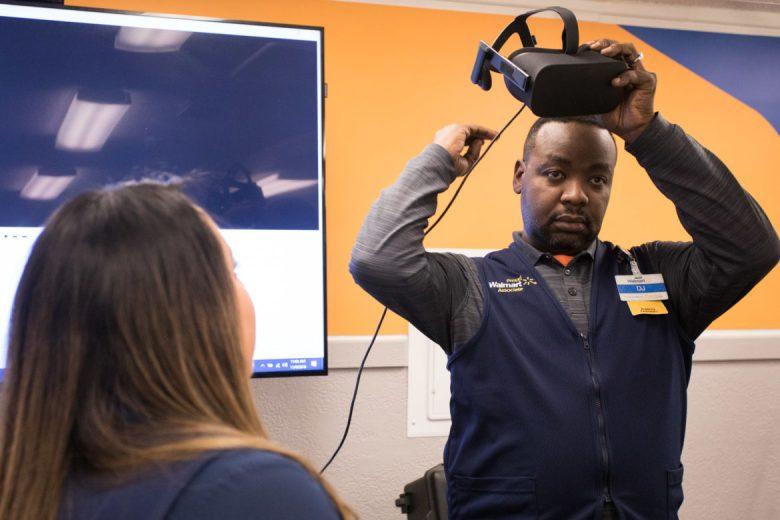 Walmart Academy Facilitator Erica Peña (left) watches as Walmart Academy Facilitator DJ Ddungu puts on a VR headset.