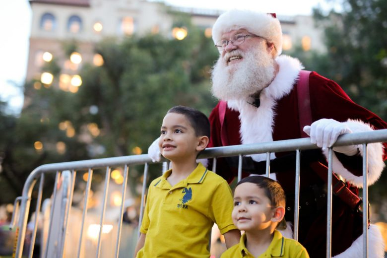 Santa Claus poses for photos with attendees at the H-E-B Christmas Tree Lighting at Travis Park.