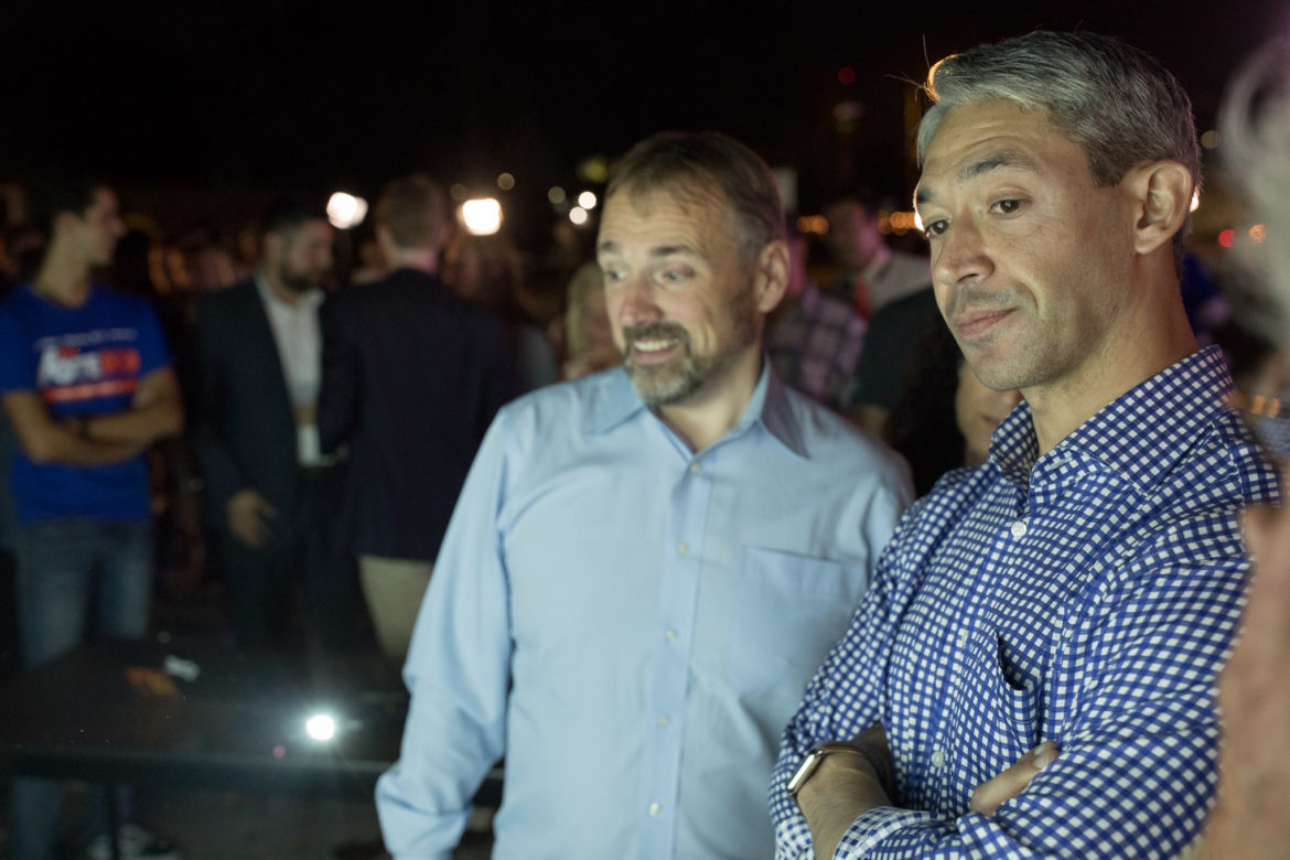 Mayor Ron Nirenberg watches poll results with Go Vote No campaign manager Christian Archer.