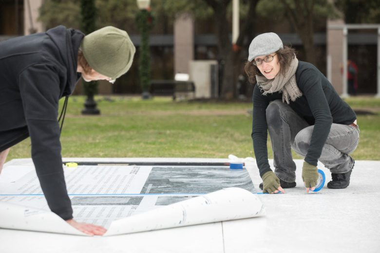 Emily Fleisher (right) and her husband Jonathan Hudak work to assemble the mural for her installation.