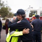 SAFD Captain Brian Stanush hugs a fellow firefighter before the trip.