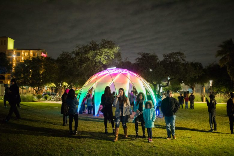 Luminaria attendees walk alongside a large colored dome at Yanaguana Garden.