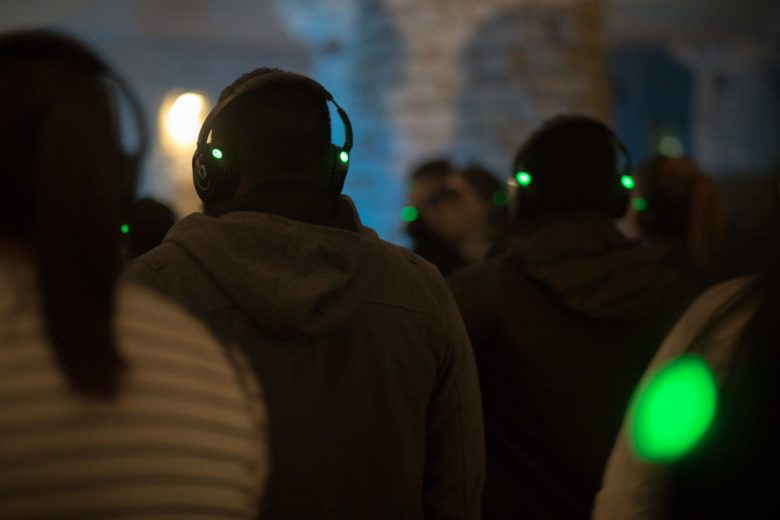 Wireless headphones lit with small green lights were worn by attendees in the grotto during the performance.