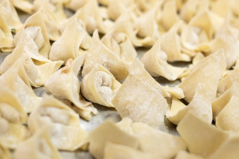 Original hand-folded wontons are prepared for cooking.