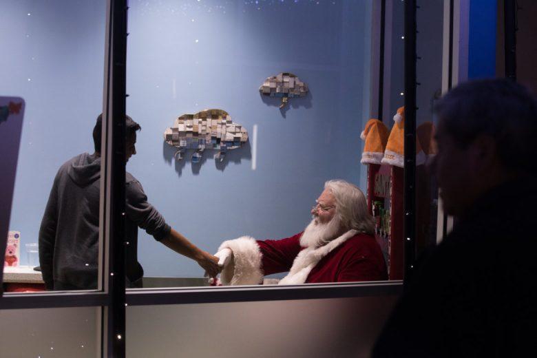 Santa Dan Balcar greets guests at the Whataburger Christmas party at the DoSeum.
