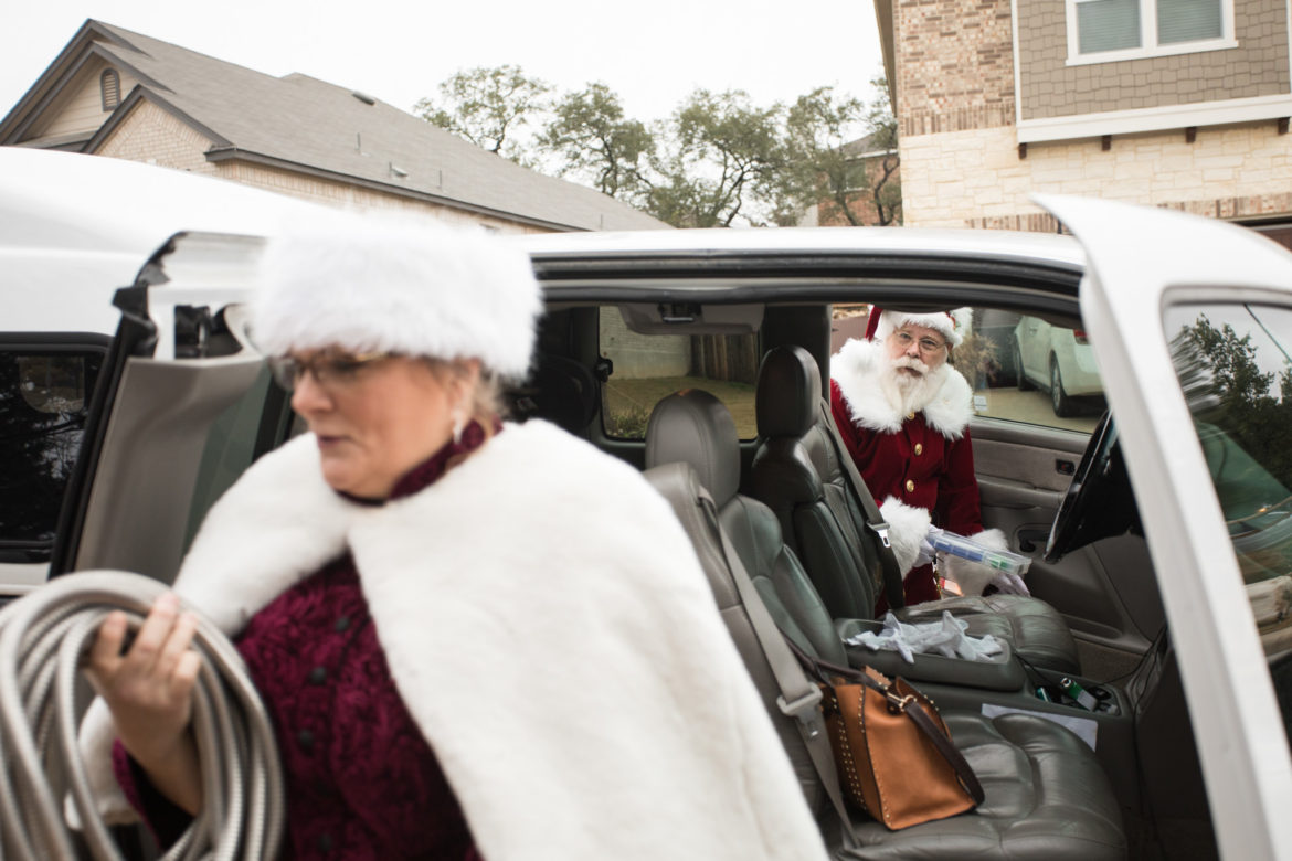 Laura Hotchkiss, dressed as Mrs. Claus, cleans out the truck as Mark Hotchkiss, dressed as Santa, prepares to drive to a neighborhood holiday party.