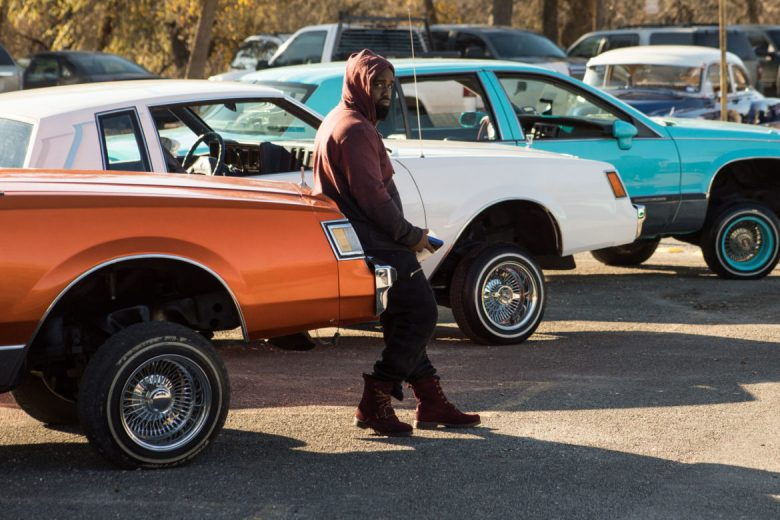 A young man leans against a car at Santa's Cruisers.