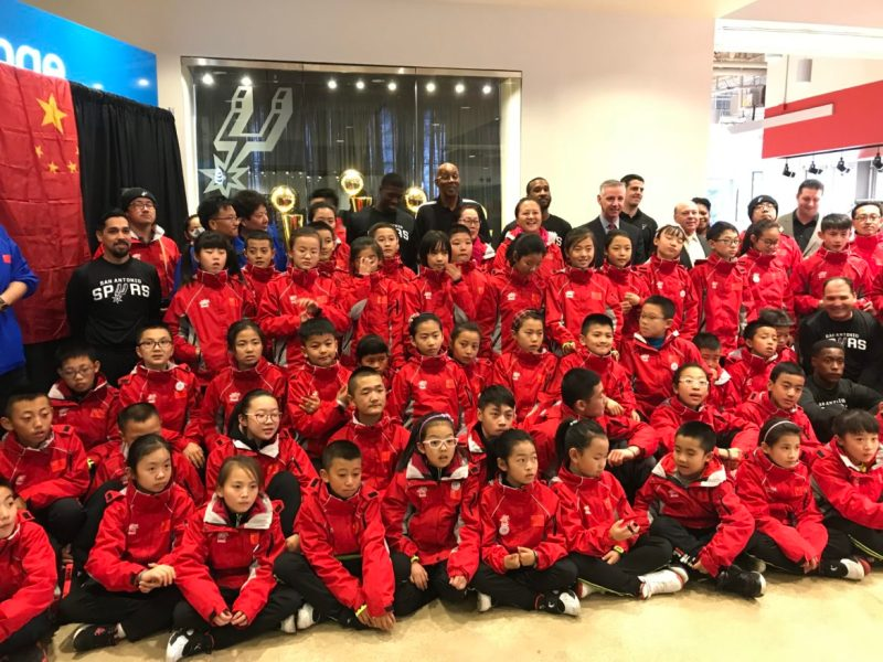 Chinese camp attendees all with a love for basketball pose for a photo in front of the Spurs championship trophies at the AT&T Center.