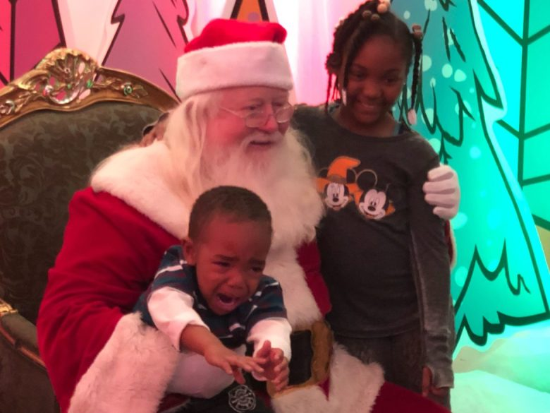 She is happy, but her brother isn't, as Santa Claus welcomes children at the 2018 HoHo Hope for the Holidays dinner at the Haven for Hope.