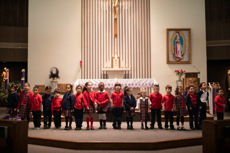 1st and 2nd grade performers stand in a line as they practice singing holiday themed songs for the show.