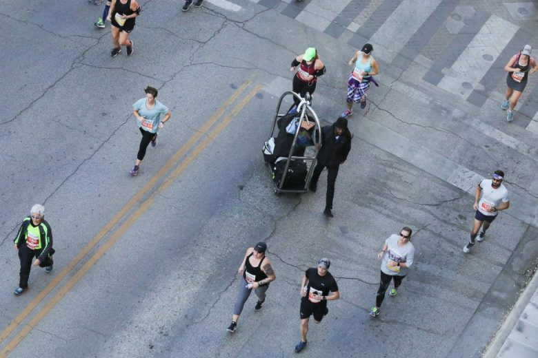 A hotel luggage cart is pushed through the Rock 'n' Roll marathon.