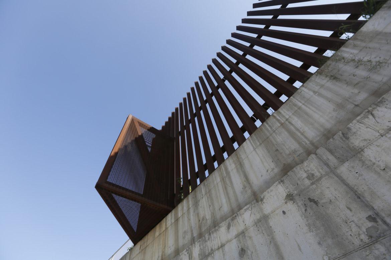 Steel bollard can be seen atop a concrete wall as it lines the banks of the Rio Grande near McAllen, Texas.