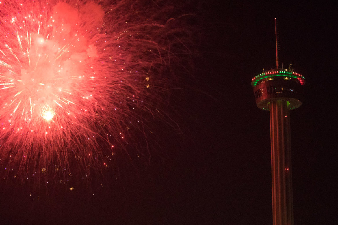 Fireworks explode next to the Tower of the Americas on New Year's Eve.