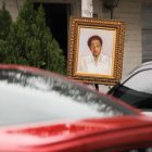 A portrait of the late Althea Barber is hung outside her home which faces the march route.