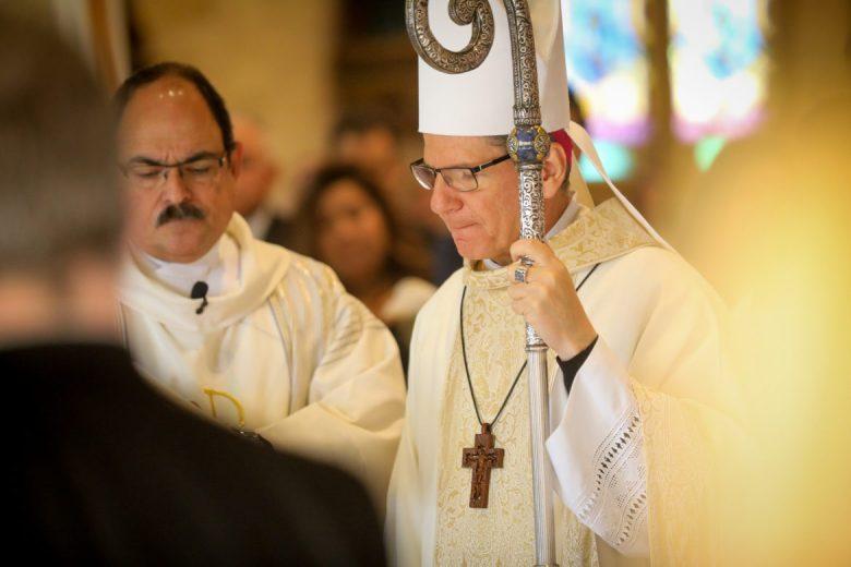Archbishop Gustavo García-Siller closes his eyes over the casket of Paul Elizondo.