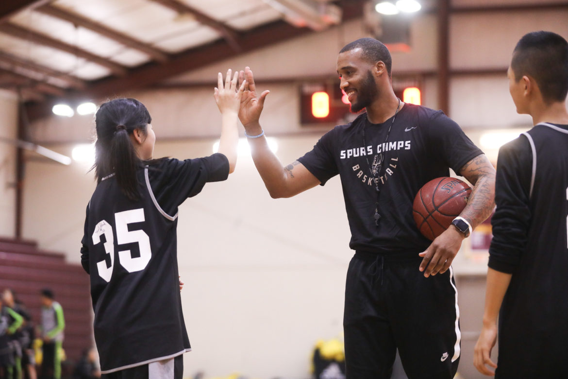 Coach Burshaud Williams high fives a student during Spurs basketball training camp.