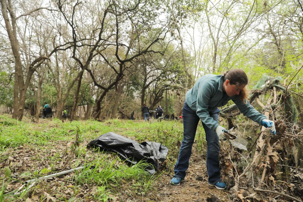 Jennifer Courtwright works to remove debris and litter from Salado Creek at Robert Tobin Park.