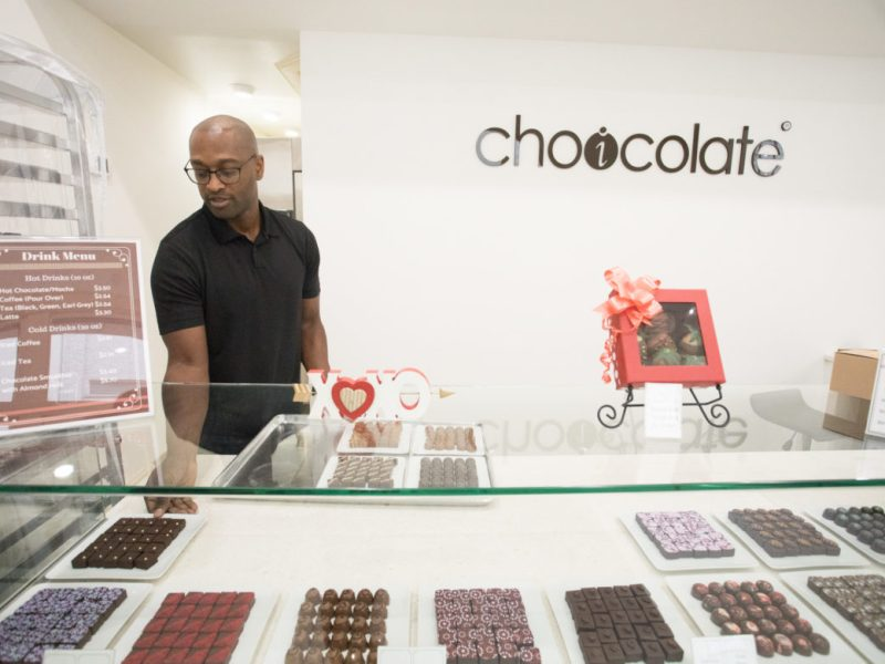 Leroy Reynolds, owner of Choicolate, straightens the displays of chocolate before opening the store.