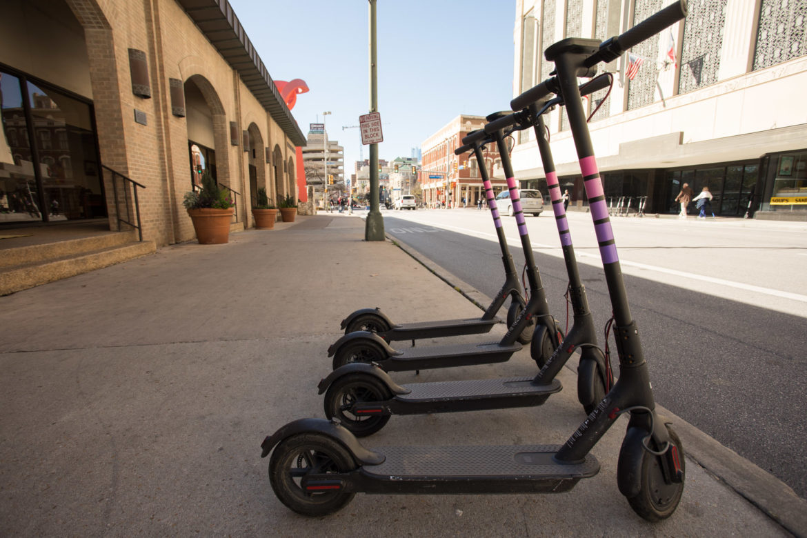Lyft scooters are lined up in front of the San Antonio Chamber of Commerce.