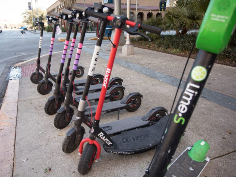Lyft scooters are lined up among other scooter brands along East Commerce Street.