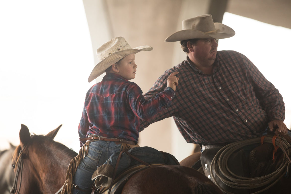 Tate Heard, 9, counts how many longhorns the cowboys have to drive with his dad, Neil Heard.